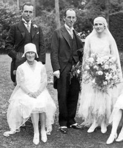 The woman to the far right is wearing a typical wedding dress from 1929. Until the late 1960s, wedding dresses reflected the styles of the day. From that time onward, wedding dresses have often been based on Victorian styles.